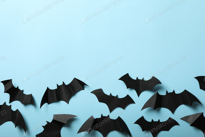 Paper bats on blue background, space for text