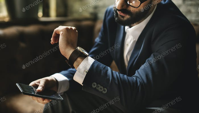 A businessman looking at a watch