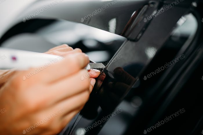 Male hand with blade, car tinting film installing