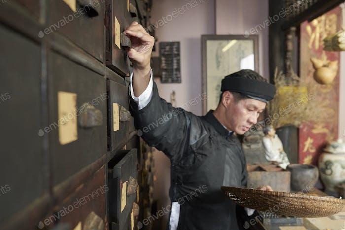 Herbal medicine practitioner opening drawer