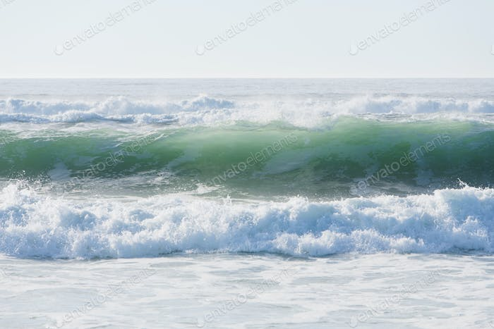 Seascape with breaking waves on sandy beach.