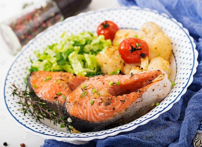 Dietary menu. Baked salmon steak with cauliflower, tomatoes and herbs.