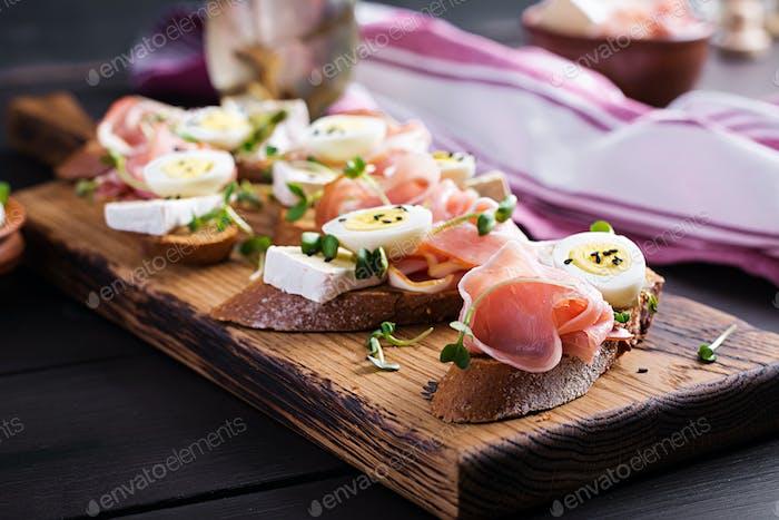 Bruschetta with prosciutto/jamon traditional Italian antipasto. Delicious snack with bread