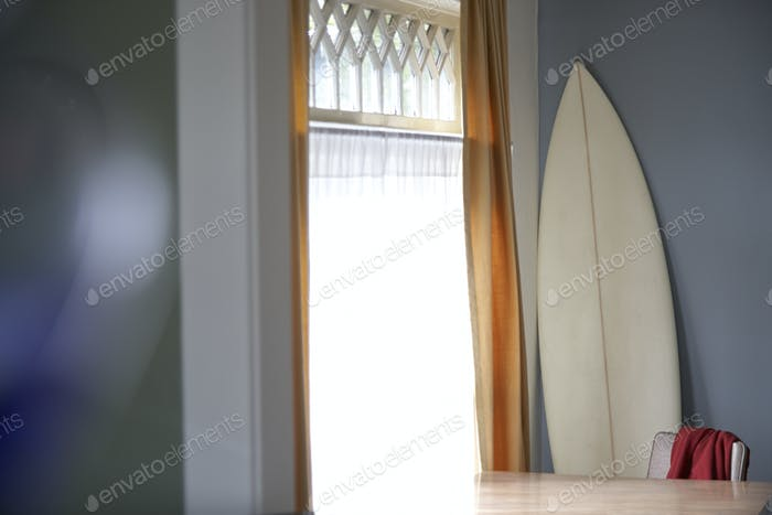 Surfboard and table at window
