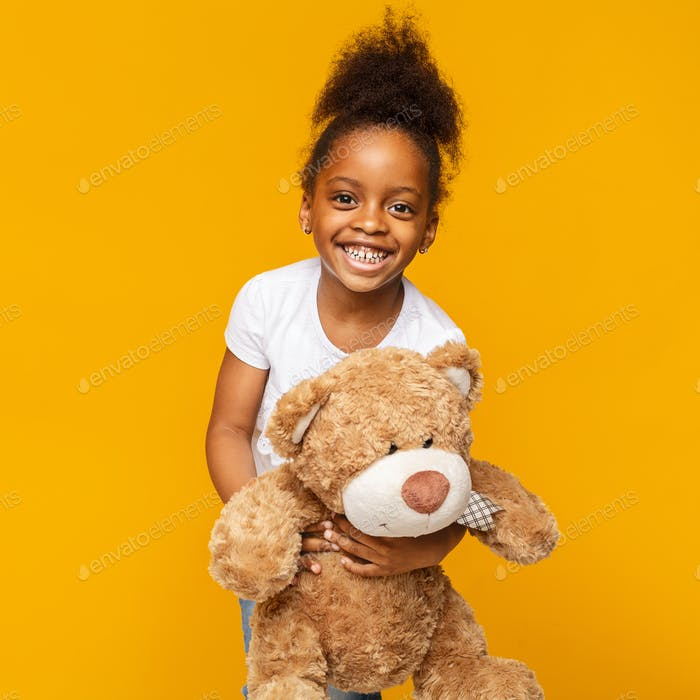 Cute african baby girl laughing with her teddy bear