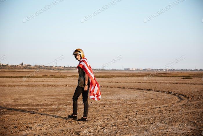 Man wearing american flag cape and golden helmet