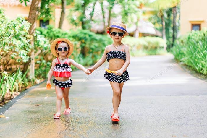 Маленькие счастливые забавные девушки имеют много удовольствия на тропических каникулах