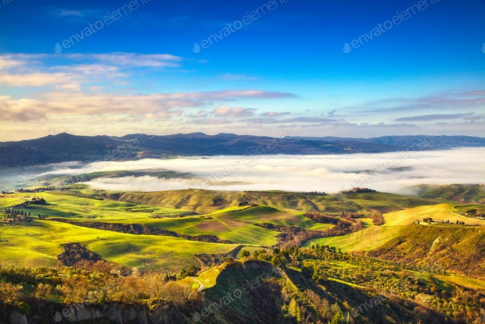 Balze of Volterra foggy morning panorama, farmlands and green fi