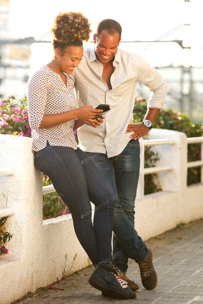 portrait of happy couple standing outside looking at mobile phon