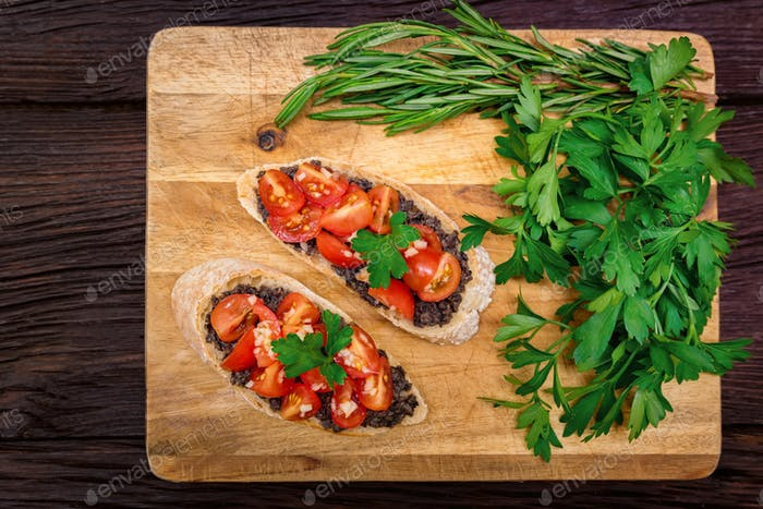 Fresh tasty bruschetta with truffle sauce, parsley and tomates. Top view