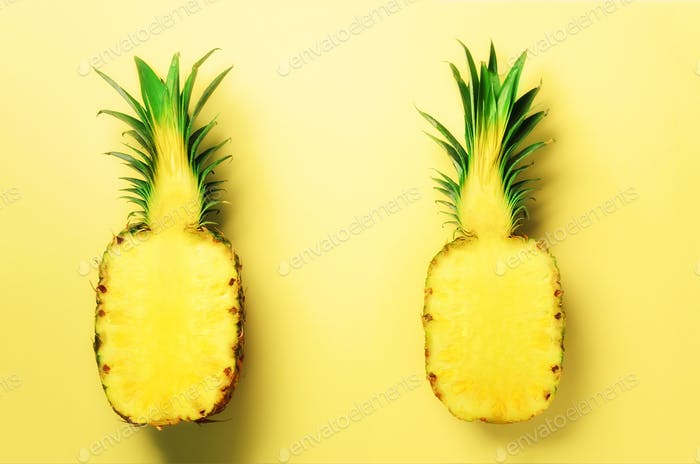 Fresh half sliced pineapple on yellow background. Top View. Copy Space. Bright pineapples pattern