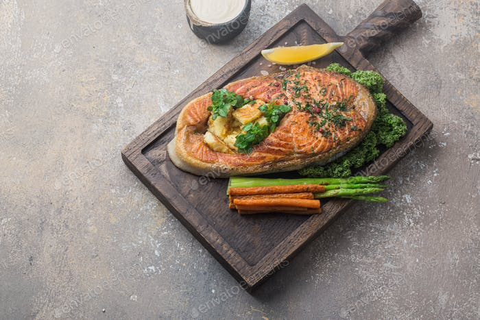 Salmon steak with vegetables on wooden board, copy space