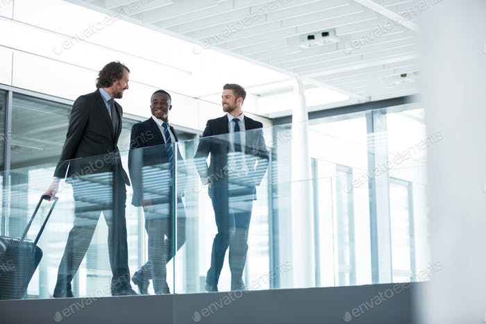 Businessman talking with colleagues while walking