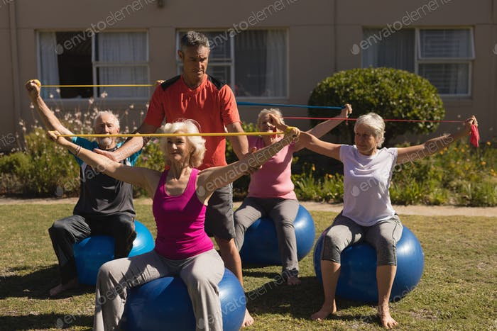 Trainer assisting senior women in performing exercise with elastic band and ball in the park