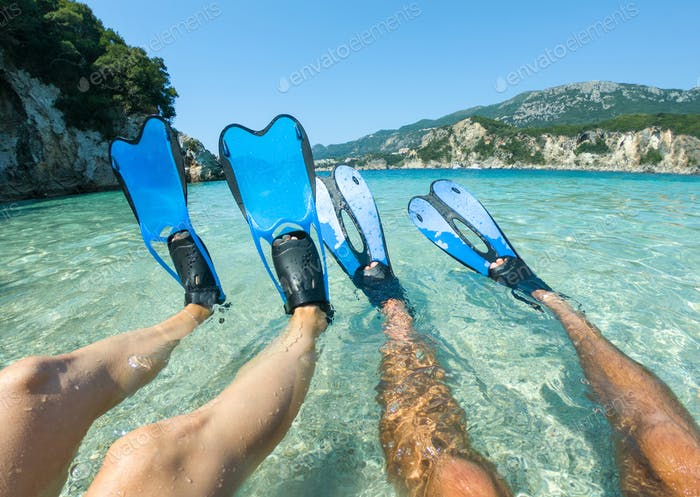 Blue snorkeling fins, flippers in crystal clear sea water. Snorkeler couple lie on the beach