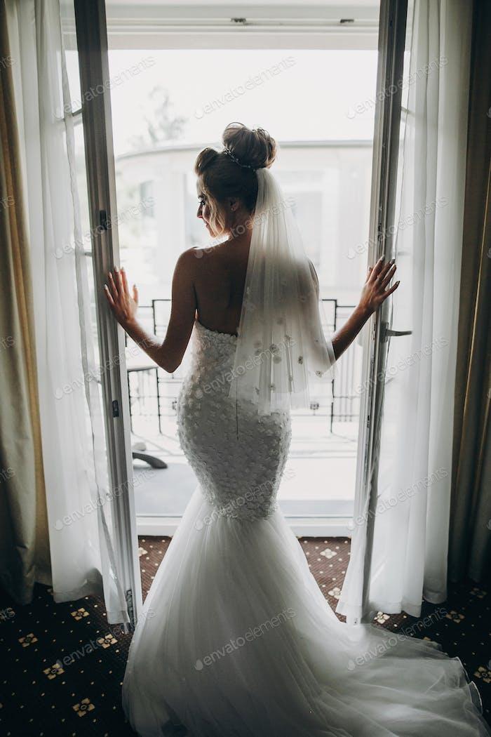 Silhouette of stylish bride opening window balcony