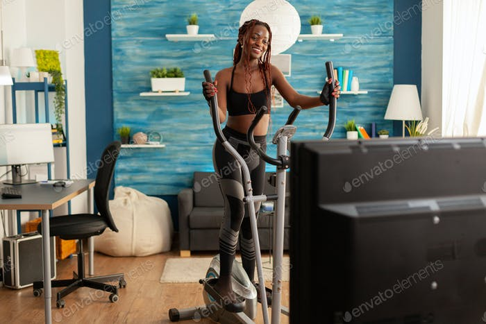 Active fitness stong black woman running on eliptical machine