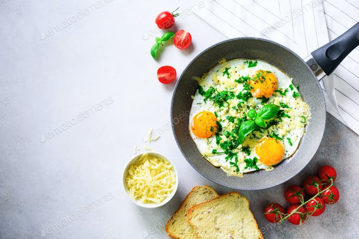 Fried eggs in pan, herbs, spices, cherry tomatoes, cheese toasts, basil for breakfast on grey