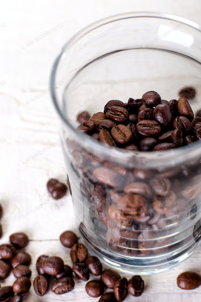 Coffee beans or grain in jar on white wooden background.