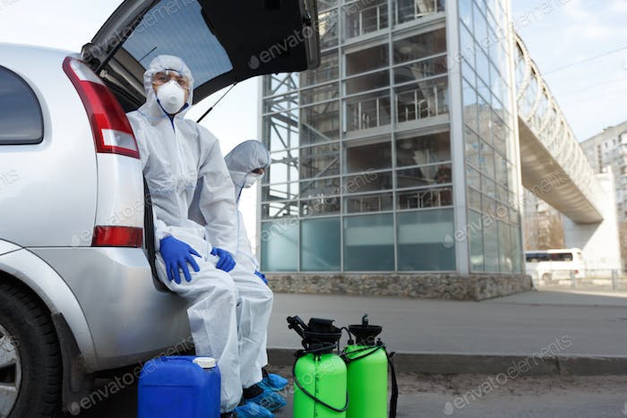 Virologists in protective suits planning to do disinfection