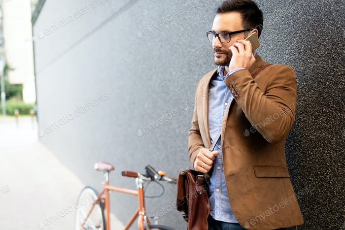 Happy businessman riding bicycle to work in morning