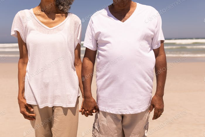 Mid section of senior couple holding hands and standing on beach in the sunshine