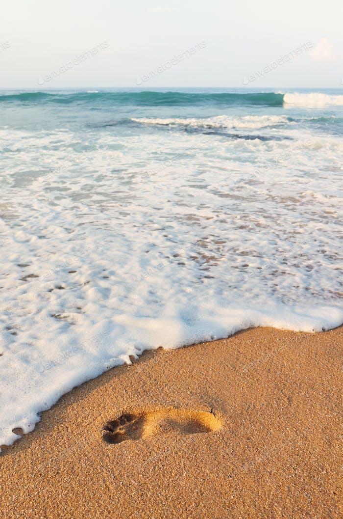Footprint on a sandy tropical beach.