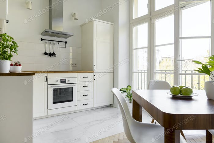 White chair at wooden dining table in simple kitchen interior wi