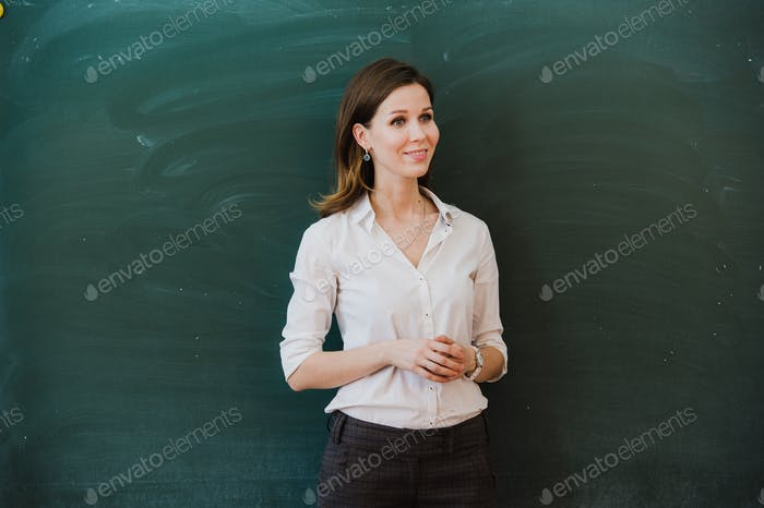 Woman pointing finger at blank board. School teacher pointing the finger at a blank board. Student