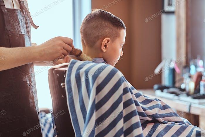 Ruhige kleine Schuljunge bereitet sich auf die Schule im trendigen Friseurladen vor