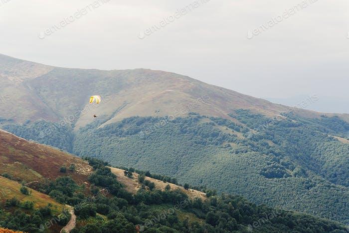 Fallschirm Fallschirmspringer fliegen in Wolken an der Spitze der Berge mit herrlicher Aussicht
