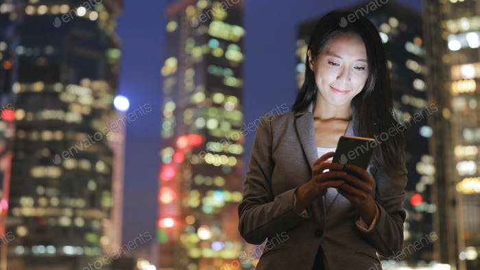 Business woman sending sms on cellphone at night