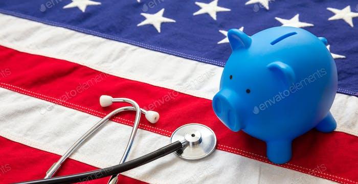 US of America health budget. Medical stethoscope and piggy bank on a USA flag, closeup view.