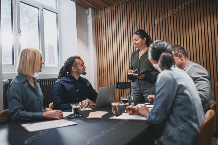 Smiling businesswoman meeting with colleageus in an office boardroom