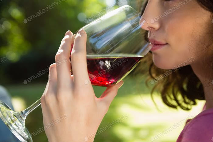 Woman drinking glass of red wine in park