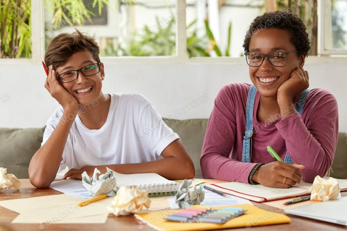 Smiling dark skinned woman gives good advice to male classmate, talk about common homework, write do