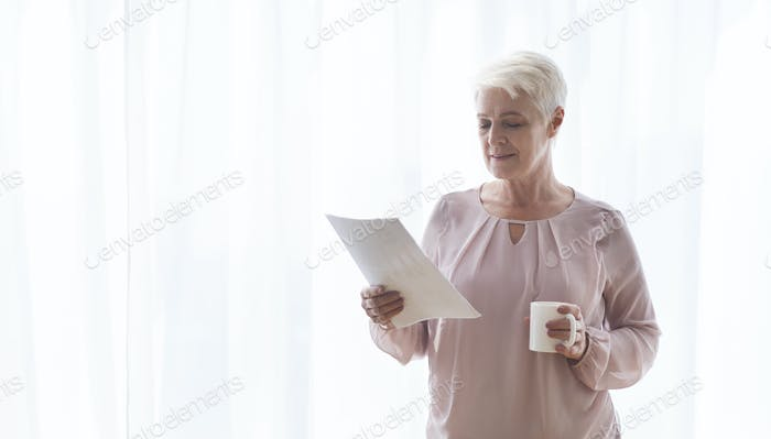 Old female author reading manuscript and drinking tea