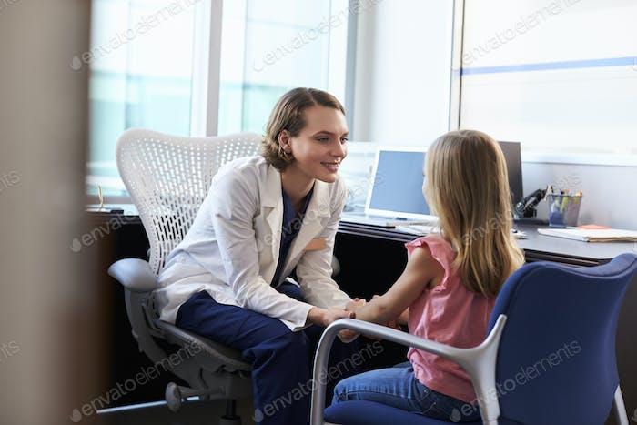 Kinderarzt im Gespräch mit Kind im Krankenhaus