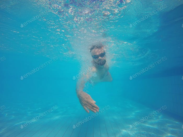 Beard man with glasses swimming under water in the pool