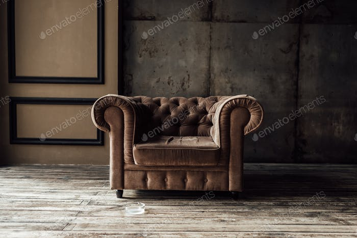 luxurious brown armchair and ashtray on floor in loft interior