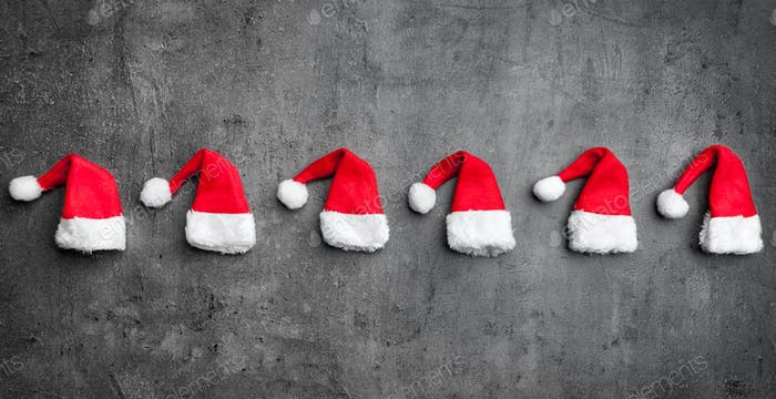 Christmas Santa hats on rustic background with copy space