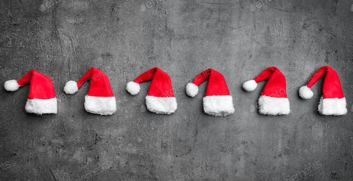 Sombreros de Papá Noel de Navidad sobre Fondo rústico con espacio de copia
