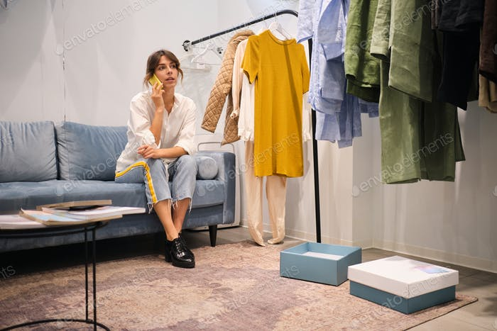 Young casual fashion designer confidently talking on cellphone on sofa in showroom