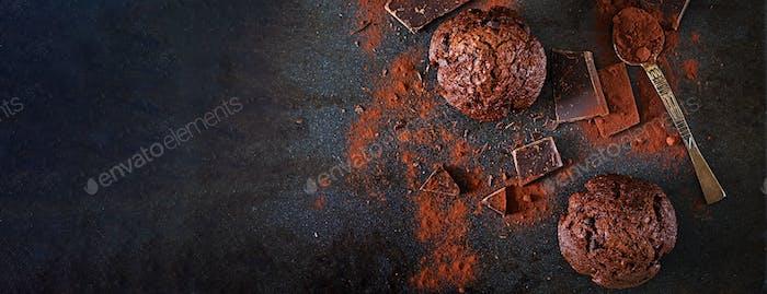 Schokoladenmuffin auf dunklem Hintergrund. Draufsicht. Banner. Flache Lag
