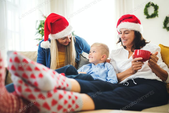 A small boy with mother and grandmother with Santa hat at home at Christmas time.
