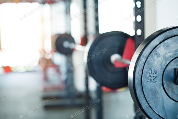 Metal heavy barbell in holder in modern gym.