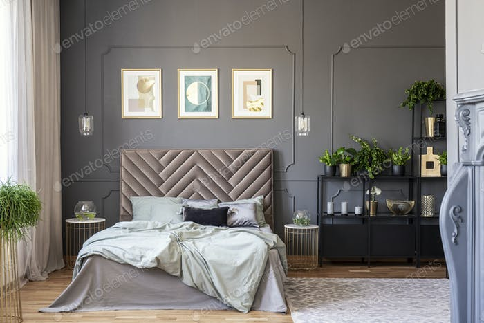 Dark bedroom interior with a comfy double bed, posters, black sh