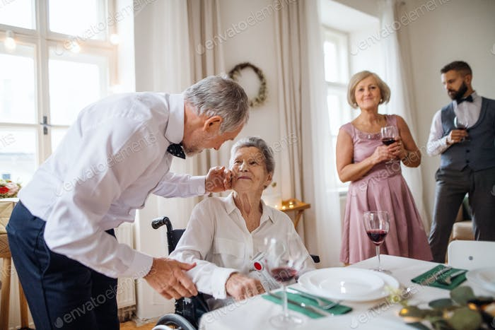 An elderly grandmother in a wheelchair celebrating birthday with family, party concept.