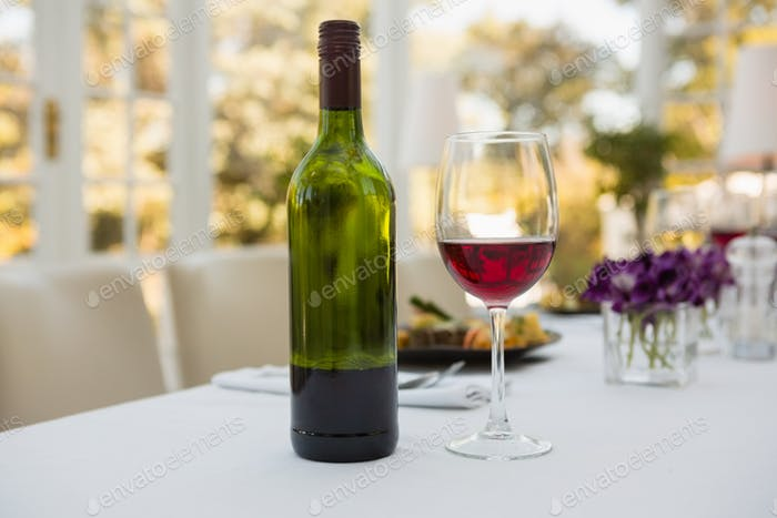 Wineglass and bottle on table in restaurant