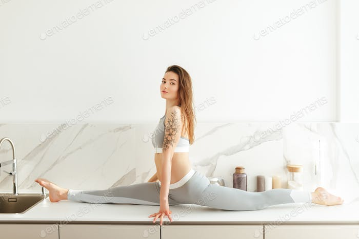 Beautiful lady in sporty clothing dreamily looking in camera practicing fitness on kitchen counter